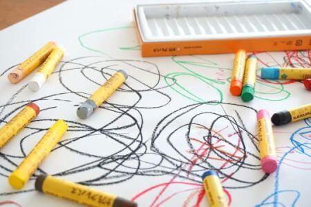 Na zdjęciu dziecięcy rysunek i rozsypane kredki.