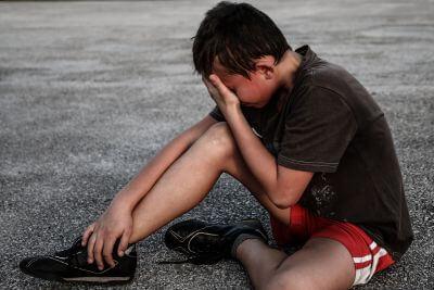 Na zdjęciu chłopiec siedzący na bieżni. Zasłania ręką oczy, prawdopodobnie płacze.