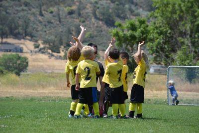 Na zdjęciu grupka dzieci w strojach piłkarskich cieszy się z wygranego meczu